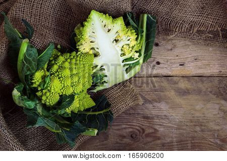 Roman caulifloweror Romanesco broccoli whole and half on a rustic wood top view from above with copy space healthy vegetable Brassica oleracea bred near Rome
