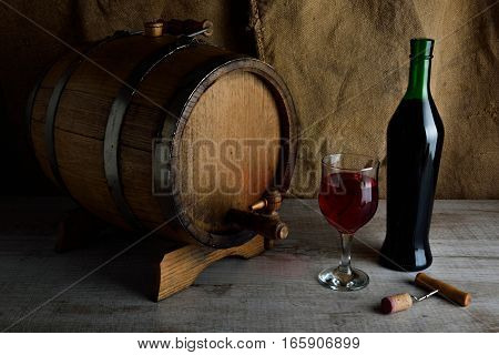 cask of wine on a wooden background with a glass of wine