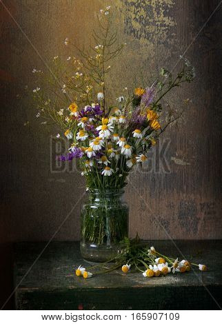 Still life with daisies in vase on a wooden table