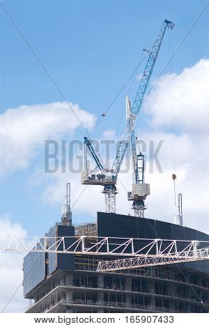 Big hoisting tower cranes and top of construction building