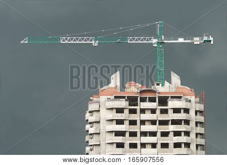 Big hoisting tower crane above top of construction building over stormy sky