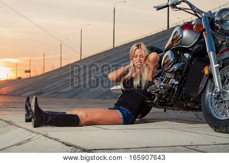 Young sexy blonde is sitting near her motorcycle on the background of a summer sunset