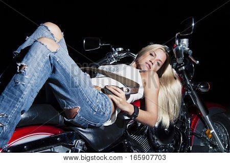 Young sexy blonde is lying on her motorcycle