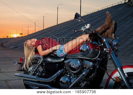 Young sexy blonde is lying on her motorcycle on the background of a summer sunset