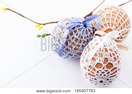 Holiday three easter eggs in handmade knitted bags with spring decor on white. Selective focus.