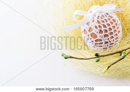 Easter egg in knitted white bag in homemade yellow nest with spring decor. Selective focus.