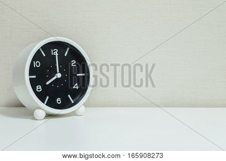 Closeup black and white alarm clock for decorate in 8 o'clock on white wood desk and cream wallpaper textured background with copy space