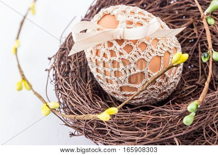 Holiday easter egg in handmade knitted bag in nest with spring decor. Selective focus.