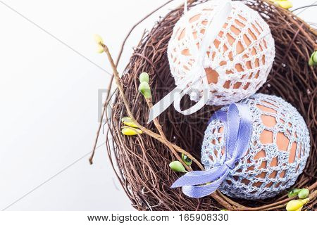 Holiday easter eggs in handmade knitted bags in brown nest with spring decor. Selective focus.