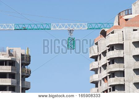 Construction frame on hoisting crane between two buildings