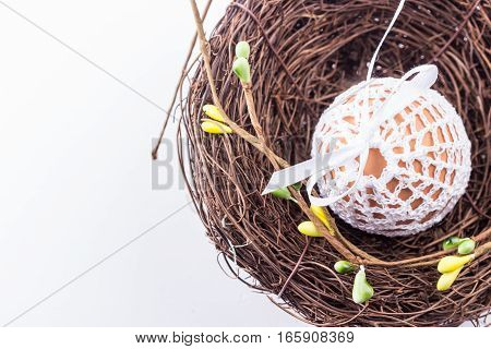 Easter egg in handmade knitted white bag in nest with spring decor. Selective focus.