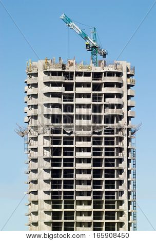 Hoisting tower crane in building action vertical view
