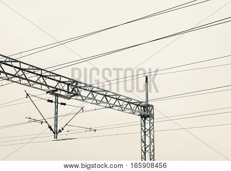 Abstract composition of railway electric wires, cloudy sky in background.