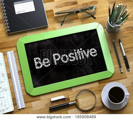 Business Concept - Be Positive Handwritten on Green Small Chalkboard. Top View Composition with Chalkboard and Office Supplies on Office Desk. Small Chalkboard with Be Positive. 3d Rendering.