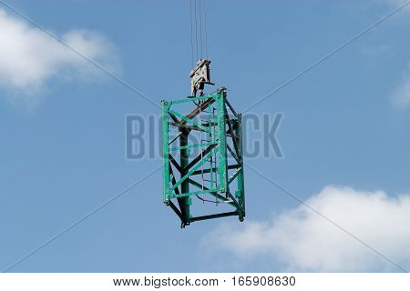 Green construction frame on crane screw over blue sky