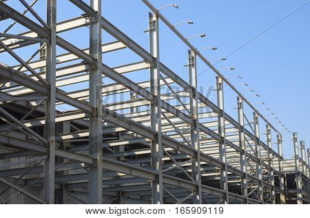Industrial building construction frames over clear blue sky
