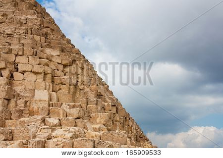 Fragment of the Great pyramids on the background of clouds