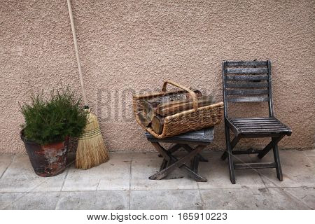 Vintage things: old French garden wooden chair, folding stool, wicker basket with firewood for fireplace (stove), broom, large clay pot with flowers. background - yellow pink walls. Provence. France.