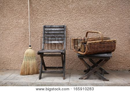 Vintage things: old French garden wooden chair and folding stool and wicker basket with firewood for the fireplace or stove and broom. Against the background of yellow pink walls. Provence. France.