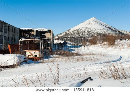 Abandoned settlement with decayed buildings and old destroyed bus in Northern Kolyma winter view