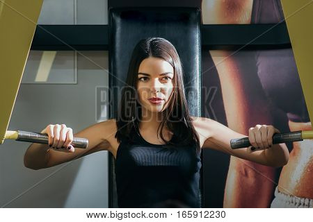 Cute girl is engaged in sports gym