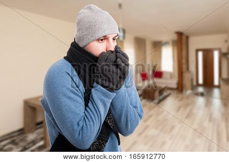 Young Man Feeling Cold And Warming His Hands
