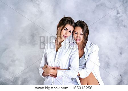 Closeup ofTwo young brunette sisters in white shirts holding each other and looking on camera