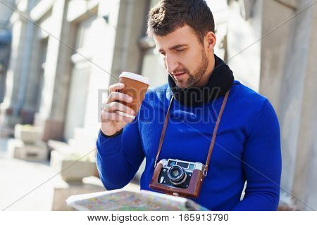 man with a camera drinking coffee while reading