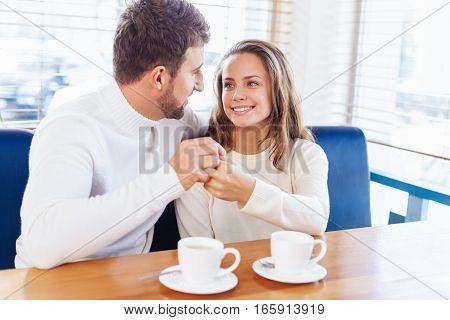 Candid image of young couple smiling in a coffee shop