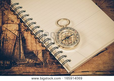 compass on the note book with old map