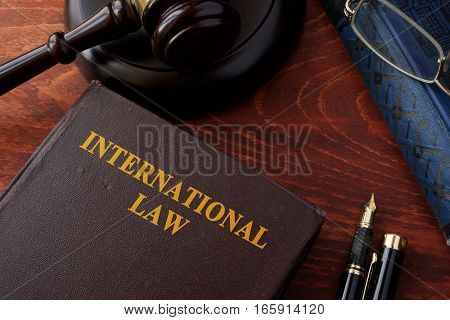 Book with title International law and a gavel.