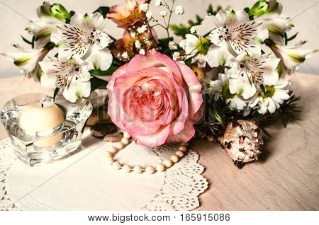 Alstroemerias with yellow-pink rose,beads,crystal candlestick with patterned napkin on wooden table