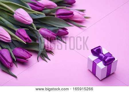 Box with a gift, bouquet of beautiful flowers, buds of spring tulips, bow from satin, holiday items for congratulations