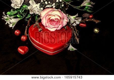 Red box heart with chocolates and bouquet from white flowers,rose and dry twigs on blackplank background