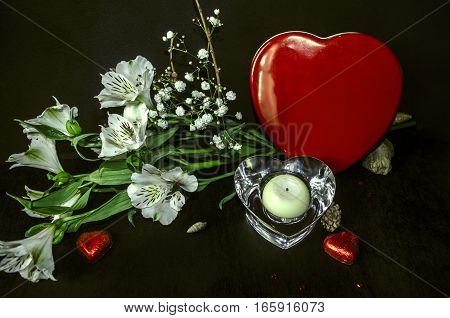 Crystal candlestick,bouquet from white flowers and chocolates in red box heart