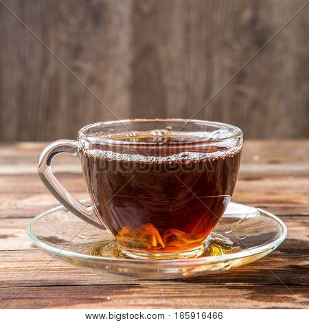 Glass cup of tea on brown wood table