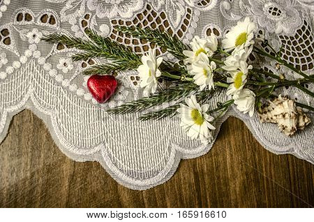 White asters with coniferous sprig and chocolate red heart on white lacy napkin