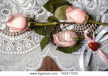 Bouquet from buds of pink roses and red heart with ribbons on lace tablecloth