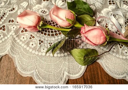 Bouquet from buds of pink roses with lace tablecloth on dark wooden table