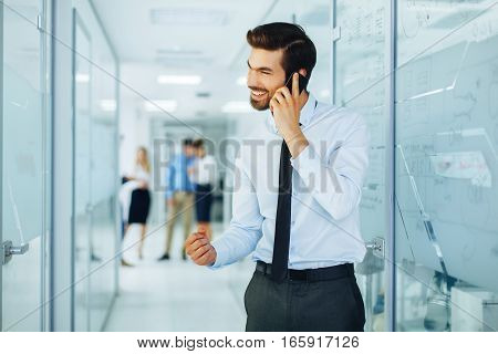 Young businessman on the phone with a group of people behind out of focus