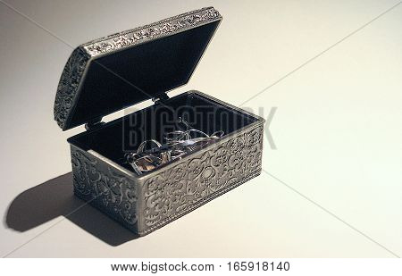 An open pewter jewellery box containing silver trinkets in the form of an ornate treasure chest shot with a single side light against a white background with copy space.