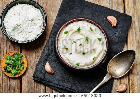 Ricotta roasted garlic mashed cauliflower on wood background