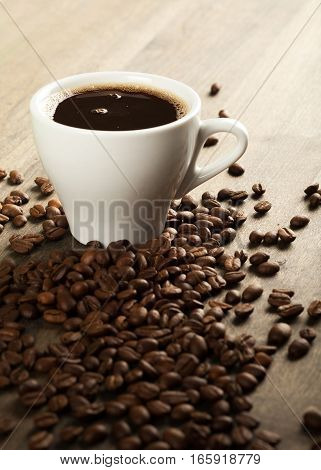 Black coffee in a mug surrounded by coffee beans