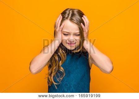 The face of sad teen girl with long hair on orange studio background