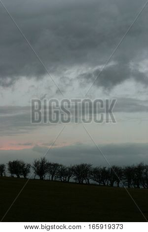 Storm clouds and a dusky sky over a silhouetted horizon, Wales, UK.