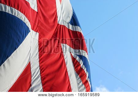 UK Union flag, also known as the Union Jack, set against blue sky copy space.