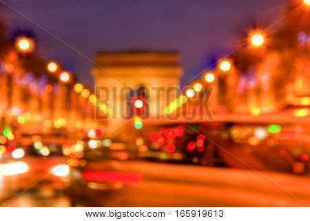 Abstract out of focus image of traffic lights with the Triumphal Arch in the background on the crowded famous boulevard Champs Elysees in Paris.