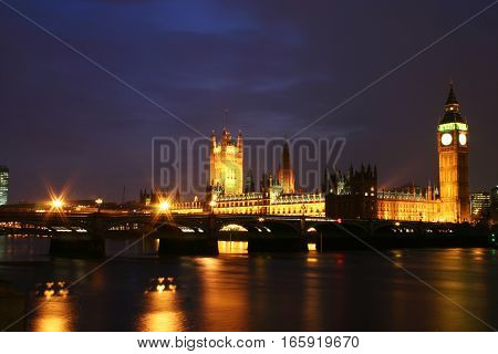 The Houses of Parliament, London, UK. View of the iconic London landmark over the River Thames at night.