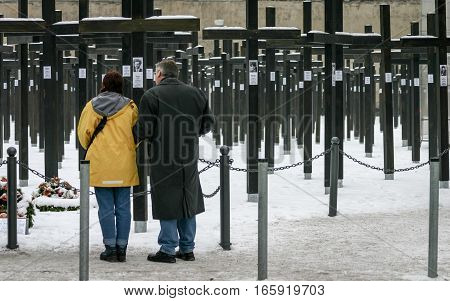 Berlin Germany - January 30 2005: a mature couple take a moment to reflect at the old Freedom Memorial paying their respects to the victims of the Berlin Wall. the memorial was dismantled in July 2005.