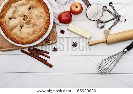Homemade apple pie dessert and ingredients shot from overhead over a white wooden table top with room for copy space.